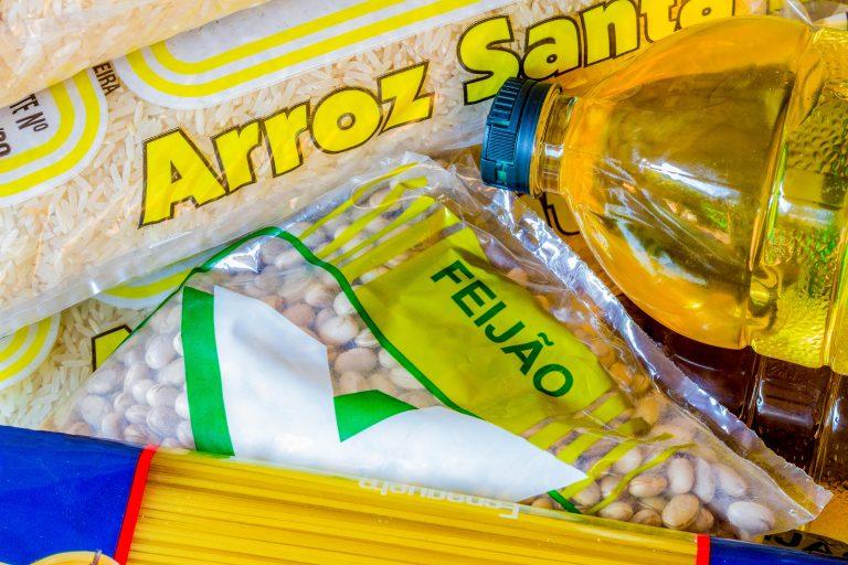 Foto de um saco de arroz, um de feijão, macarrão e óleo
