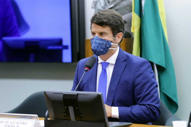 Deputado Dr. Luiz Antonio Teixeira Jr. está sentado falando ao microfone. Ele usa máscara facial e atrás dele há uma bandeira do Brasil pendurada