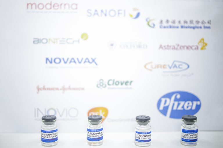 Frascos de vacinas contra Covid com banner de marcas diferentes ao fundo