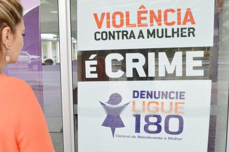 Mulher está de costas lendo um cartaz sobre violência doméstica