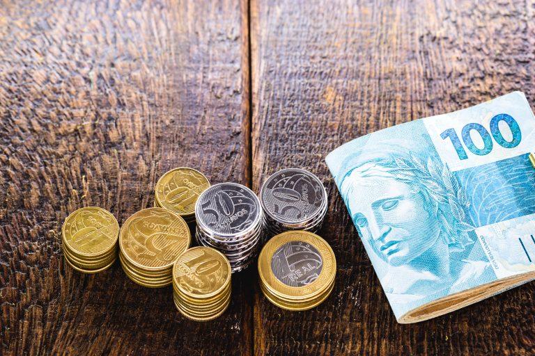 Em cima de uma mesa há várias notas de dinheiro e moedas
