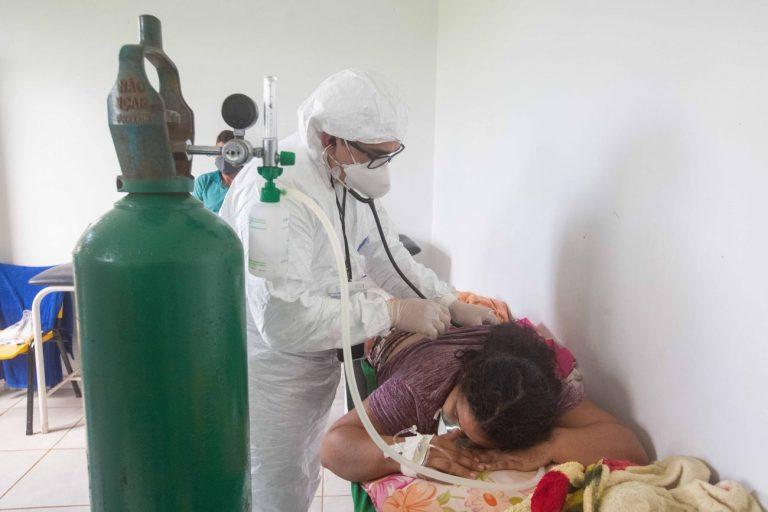 Mulher deitada de bruços respira com ajuda de oxigênio e é examinada