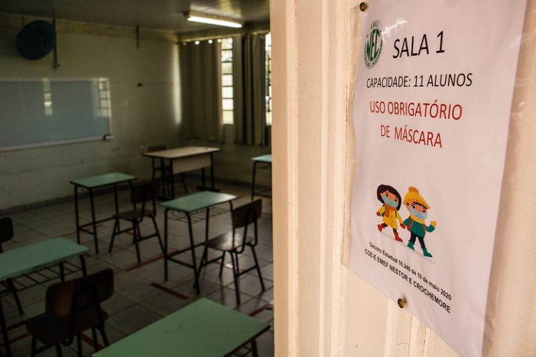 Sala de aula vazia com porta semiaberta e cartaz sobre uso obrigatório de máscara