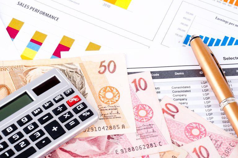 Em cima da mesa há uma calculadora, notas de dinheiro, uma caneta e vários gráficos