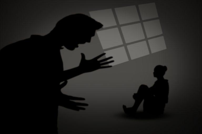 Silhueta de homem de pé gritando com mulher sentada no chão