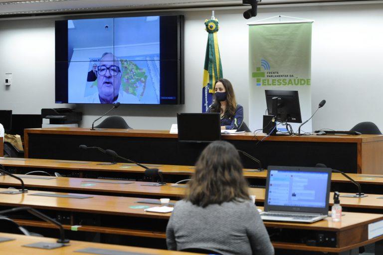 Deputados estão sentados à frente de seus computadores acompanhando um homem que fala num telão ao fundo