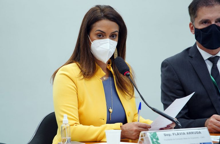 Deputada Flávia Arruda está sentada à mesa. Ela usa máscara facial e fala ao microfone