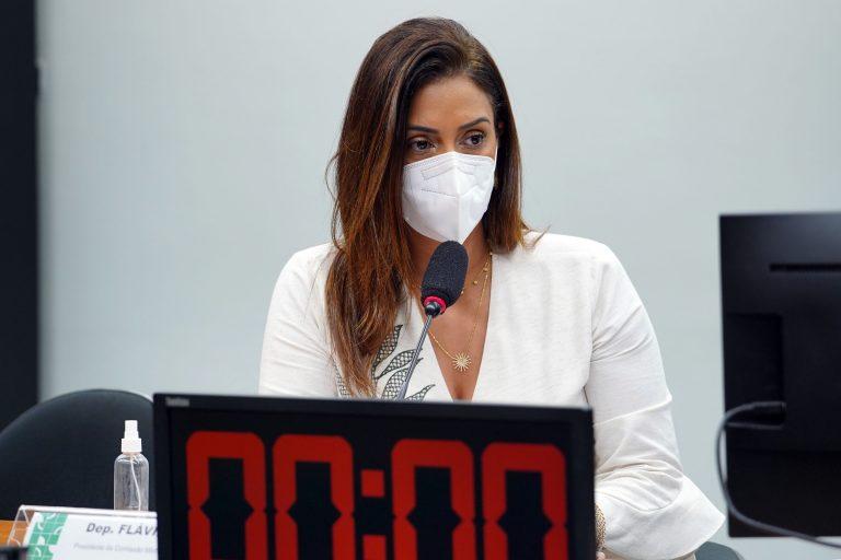 Deputada Flávia Arruda está sentada à mesa falando ao microfone. Ela usa máscara e à frente dela há um cronômetro
