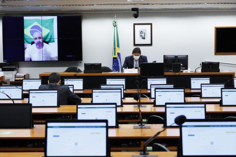 Vários computadores estão ligados em cima das mesas. Alguns deputados estão sentados acompanhando a reunião que também é transmitida em um telão