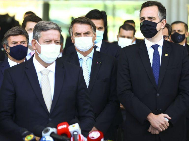 Presidentes da Câmara, da República e do Senado estão em pé, de máscara, concedendo entrevista a jornalistas