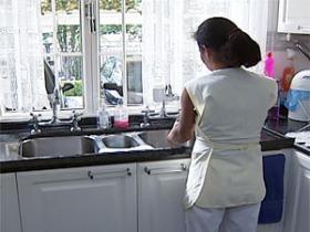 Empregada doméstica usa uniforme branco e está de costas lavando louça