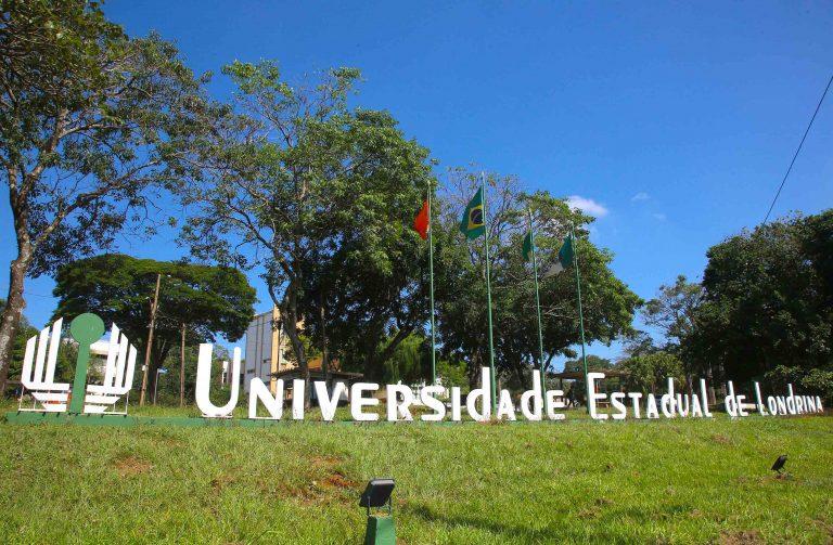 Foto de um gramado com o letreiro da Universidade de Londrina. Ao fundo, há bandeiras hasteadas