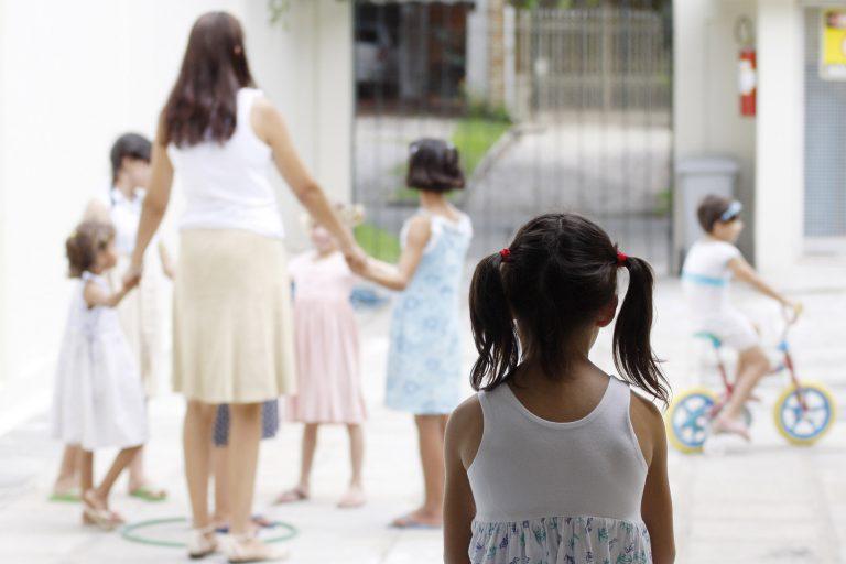 Crianças de costas em pátio com adulta