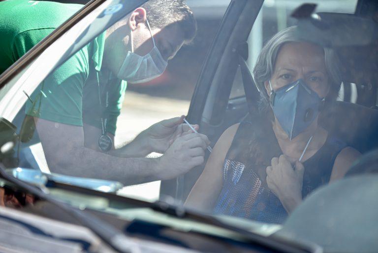Idosa está sentada no carro enquanto um enfemeiro aplica a vacina da Covid-19 nela