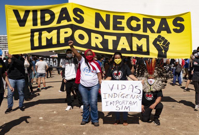 Pessoas estão na rua protestando contra o racismo. Elas seguram uma faixa onde se lê: Vidas negras importam