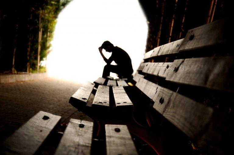 Silhueta de uma pessoa sentada num banco com a cabeça baixa. Ao fundo há uma luz forte