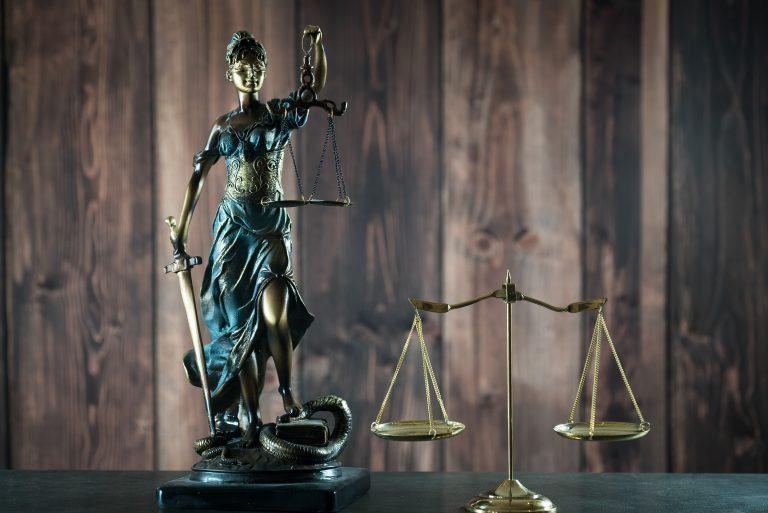 Em cima da mesa há uma estátua de uma mulher vendada com uma balança nas mãos representando a justiça
