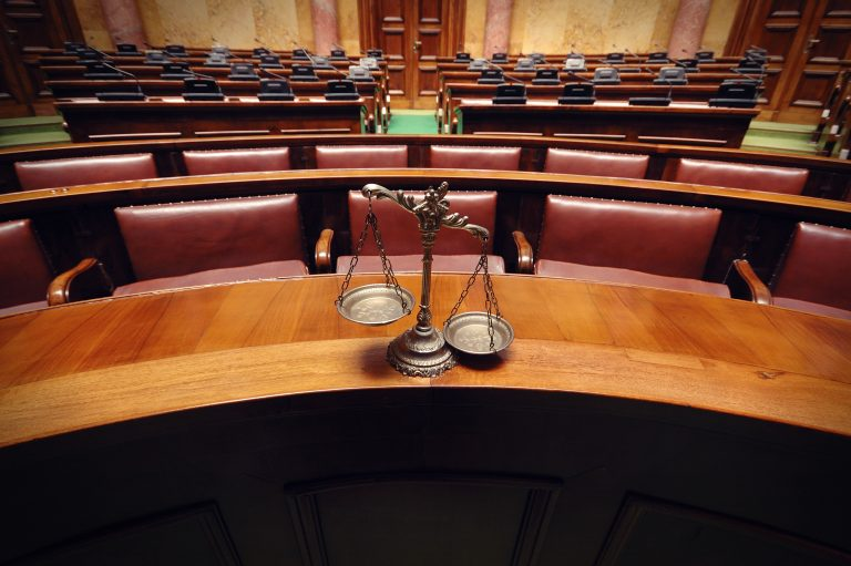Uma balança, representando a justiça, está em cima da mesa de um juiz num tribunal vazio