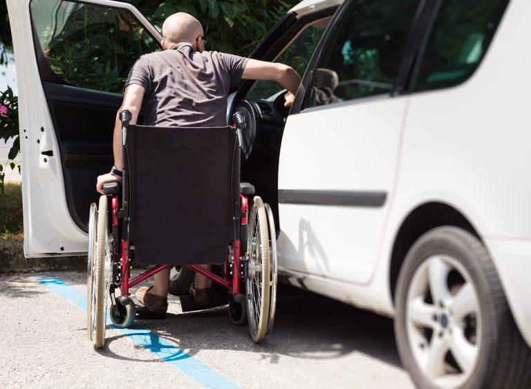 Motorista cadeirante está entrando num carro adaptado para ele dirigir
