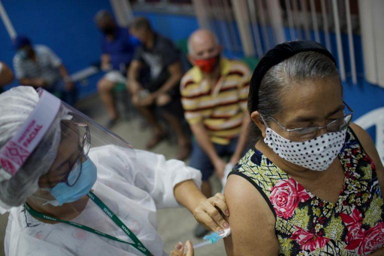 Idosa recebe vacina enquanto outras pessoas aguardam