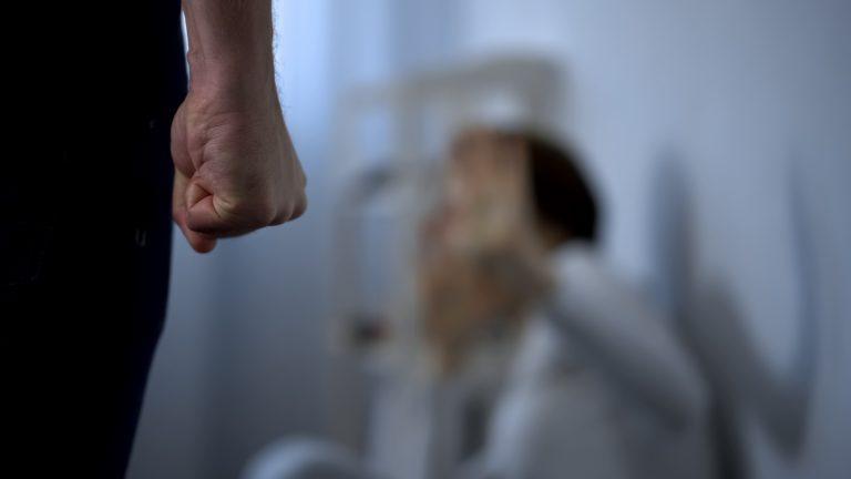 Um homem aparece de costas com o punho fechado. Ao fundo, há a imagem desfocada de uma mulher sentada no chão protendo o rosto com as mãos