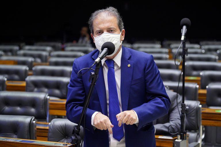 Deputado Rodrigo de Castro discursa no Plenário da Câmara. Ele está em pé à frente de várias cadeiras e usa máscara facial.