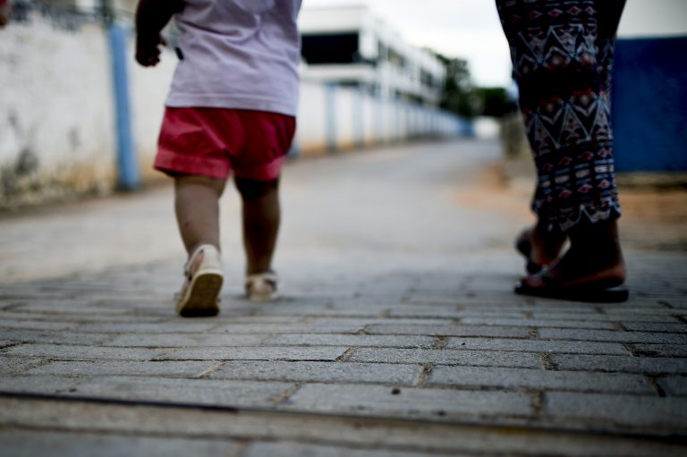 Uma criança pequena caminha ao lado de um adulto. A foto está cortada e parecem apenas as pernas e os pés das pessoas