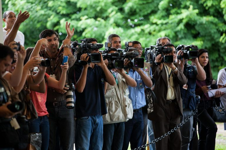 Repórteres com câmeras e celulares nas mãos e nos ombros