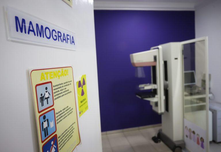 Porta de uma sala com uma placa escrito: Mamografia. Ao fundo, há o aparelho para fazer o exame