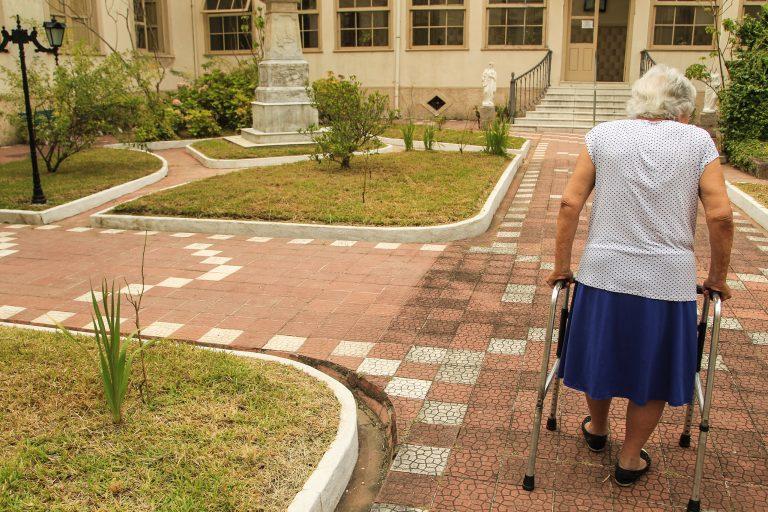 Idosa caminha num pátio com ajuda de um andador