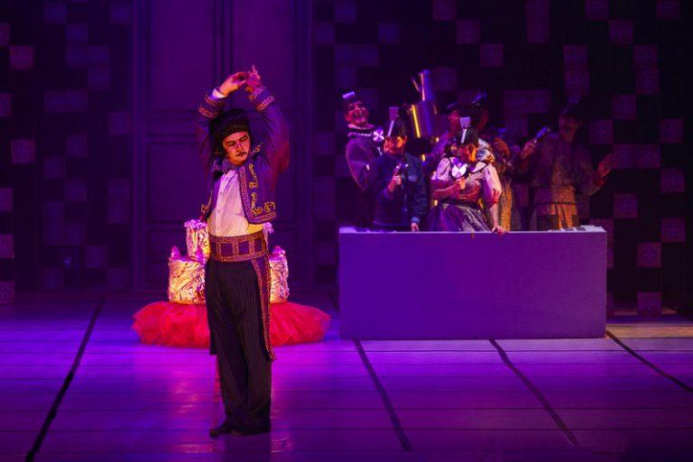 Um homem vestido de mágico está no palco de um teatro iluminado de roxo