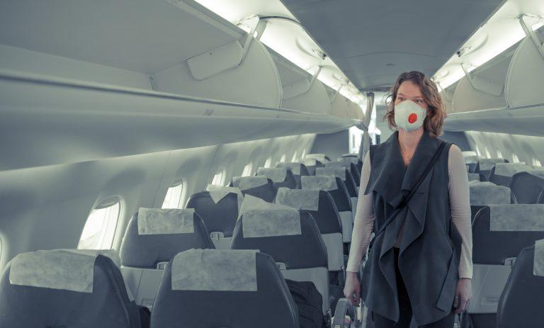 Mulher usa máscara em avião vazio