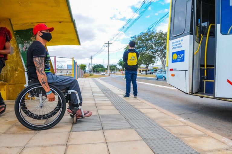 Cadeirante de máscara em ponto de ônibus