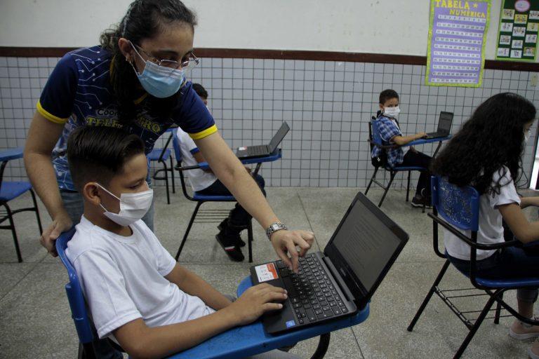 Aluno mexe num laptop com a ajuda da professora
