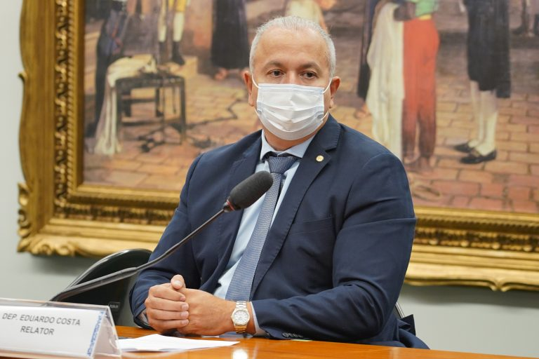 Deputado Eduardo Costa está sentado atrás de um microfone. Ele usa máscara e veste um terno escuro