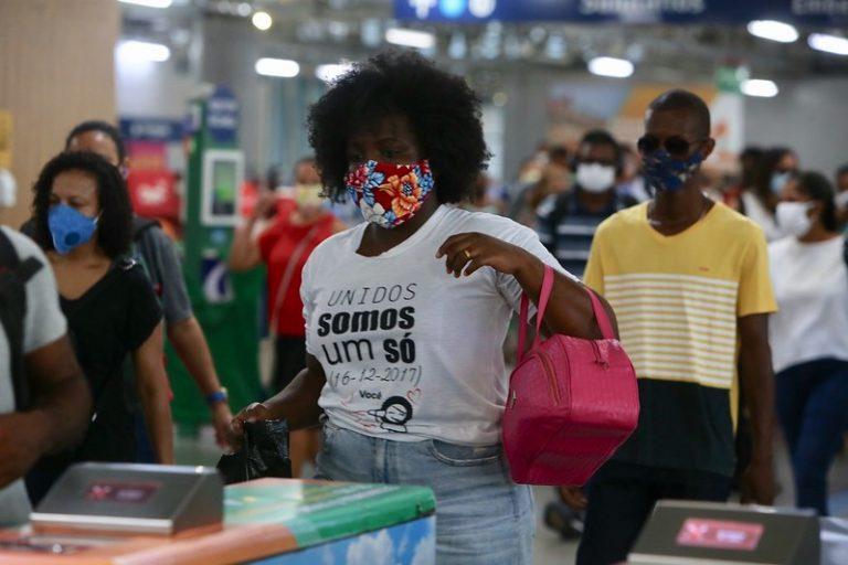 Várias pessoas estão numa estação de metrô. Todas usam máscaras