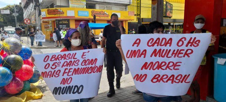 Pessoas na rua protestando contra o feminicídio. Elas seguram uma faixa onde se lê: A cada 6hs uma mulher morre no Brasil