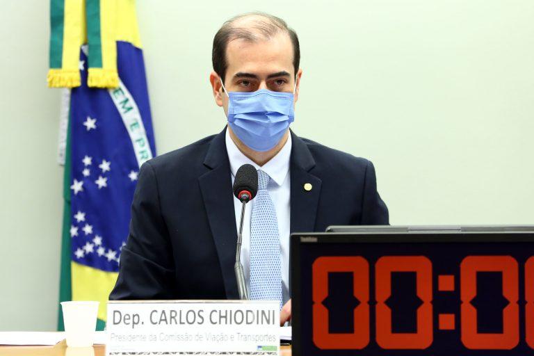 Deputado Carlos Chiodini está sentado, de máscara, e fala ao microfone