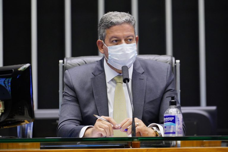 Presidente da Câmara, Arthur Lira, está sentado falando ao microfone