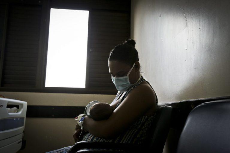 Mãe de máscara com recém-nascido no colo