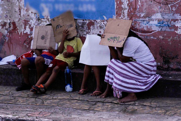 Três crianças e uma mulher estão sentadas na rua. Elas cobrem o rosto com pedaços de papelão
