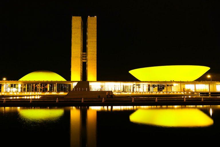 Prédio do Congresso iluminado de amarelo. Ao fundo, o céu está escuro à noite