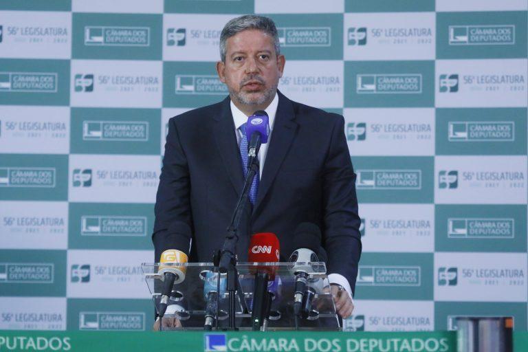 Deputado Arthur Lira, concede entrevista coletiva. Ele está em pé atrás de um púlpito com microfones de várias emissoras de rádio e TV