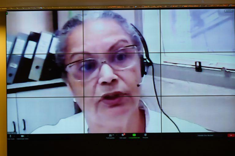 Mulher branca de óculos fala olhando para a tela do computador
