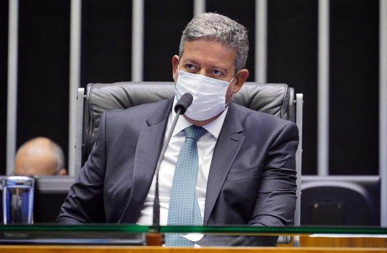 Presidente da Câmara, Arthur Lira, está sentado, de máscara, falando ao microfone