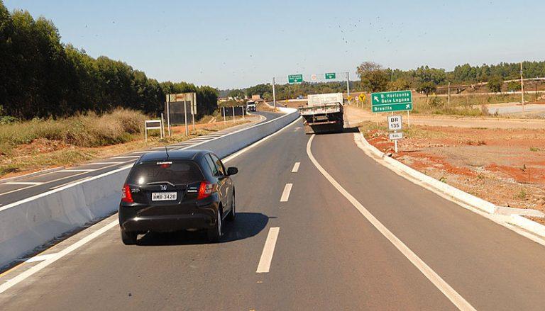 Um carro e um caminhão trafegam numa rodovia pavimentada
