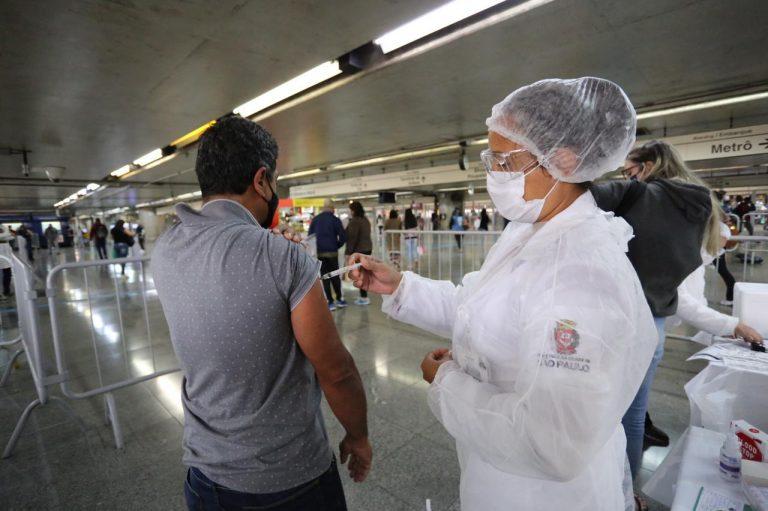 Enfermeira aplica vacina num homem numa estação de metrô