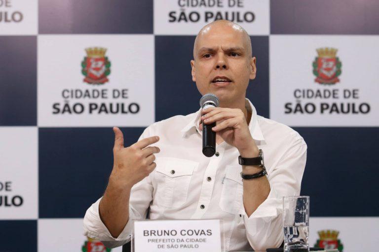 Prefeito Bruno Covas está sentando falando ao microfone. Ele está careca e usa uma camisa branca. Ao fundo há um painel escrito: Cidade de São Paulo