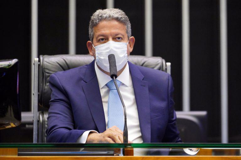 Presidente da Câmara, deputado Arthur Lira, preside sessão de votação. Ele está sentado, de máscara e fala ao microfone