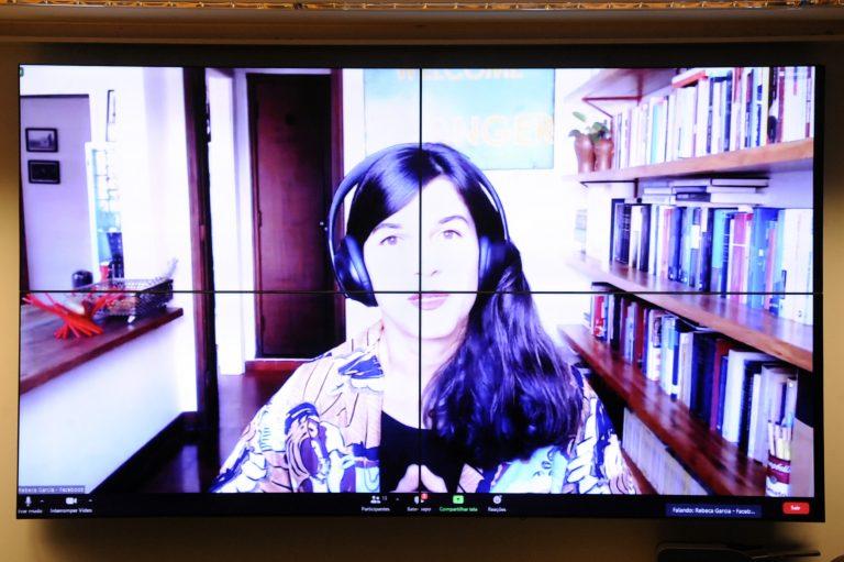 Rebeca Garcia fala olhando para a tela do computador. Ela é branca, tem o cabelo escuro e longo e usa um fone de ouvido